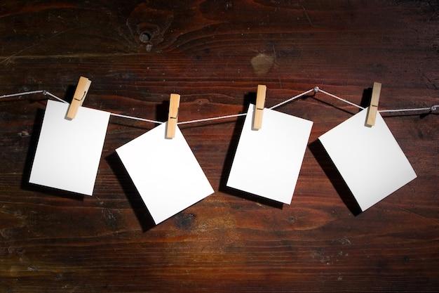 Fotopapier befestigt an seil mit kleidungsdrehungen auf holzuntergrund