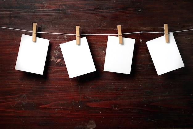 Fotopapier mit wäscheklammern auf holzuntergrund am seil befestigen
