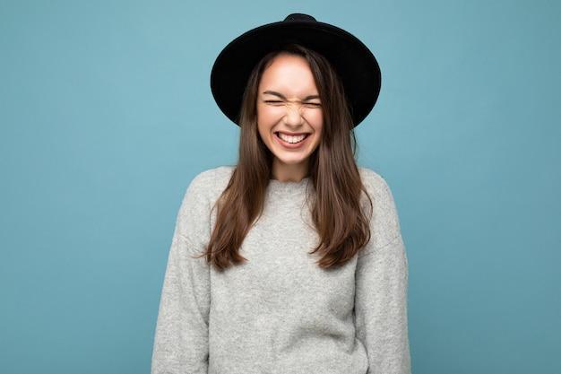 Fotoporträt der jungen schönen lächelnden brünetten frau des hippies im modischen pullover und im schwarzen hut