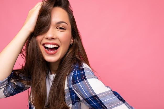 Fotoporträt der jungen schönen lächelnden brünetten hipsterfrau im trendigen blauen und weißen hemd