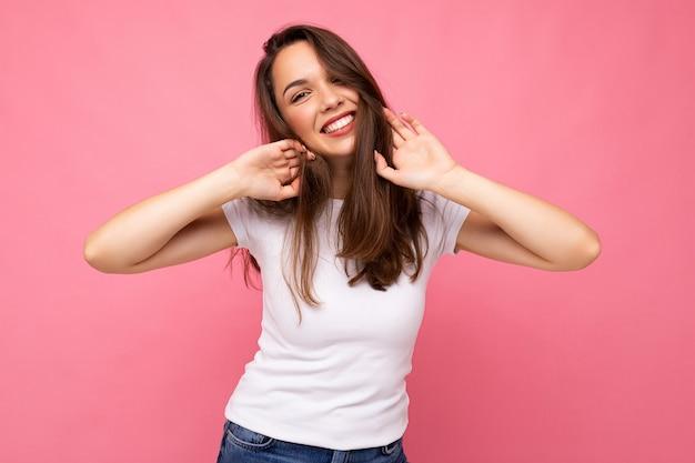 Fotoporträt der jungen schönen lächelnden brünetten hipsterfrau im weißen t-shirt mit modell. sexy