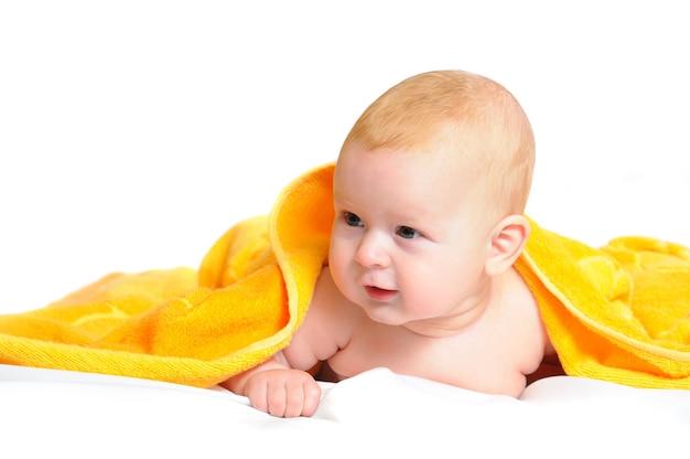 Fotoporträt des neugeborenen, das unter gelber decke liegt und zur seite schaut. auf weißem hintergrund isoliert