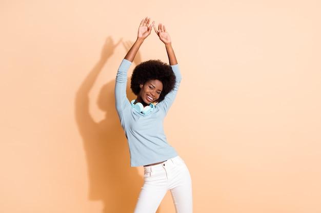 Fotoporträt einer afroamerikanischen frau, die mit beiden händen in der luft tanzt, isoliert auf pastellbeigem hintergrund