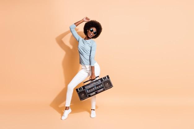 Fotoporträt einer energischen schwarzhäutigen frau, die eine boombox in einer hand hält, die isoliert auf pastellbeigem hintergrund tanzt