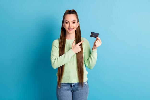 Fotoporträt einer frau, die mit dem finger auf eine plastikkarte zeigt, die auf pastellblauem hintergrund isoliert ist