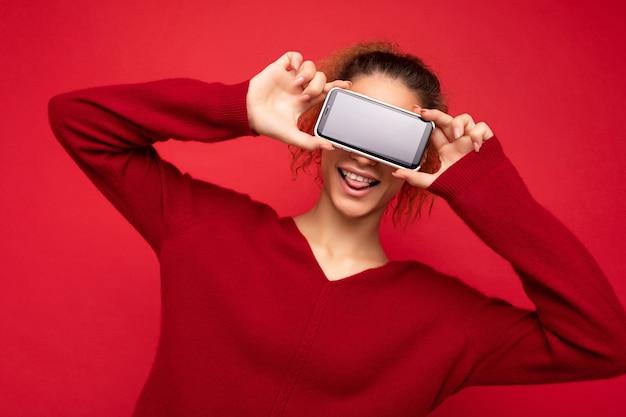 Fotoporträt einer glücklich lächelnden, lustigen jungen frau, die einen dunkelroten pullover trägt, isoliert auf rotem hintergrund, der smartphone hält und den handy-bildschirm mit leerem raum für mock-up-spaß zeigt.