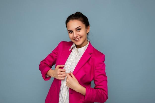 Fotoporträt einer jungen attraktiven, schönen, positiv lächelnden brünetten frau mit aufrichtigen emotionen, die ein lässiges weißes hemd und eine stilvolle rosa jacke trägt, die auf blauem hintergrund mit kopienraum isoliert ist.