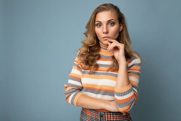 Fotoporträt einer jungen hübschen, nachdenklichen blonden frau, die einen stilvollen, bunt gestreiften pullover trägt, isoliert auf blauem hintergrund mit kopierraum und denken