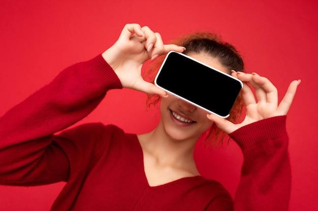 Fotoporträt einer lächelnden, fröhlichen, lustigen jungen frau, die einen dunkelroten pullover trägt, isoliert auf rotem hintergrund, der smartphone hält und den handy-bildschirm mit leerem raum für mock-up-spaß zeigt.