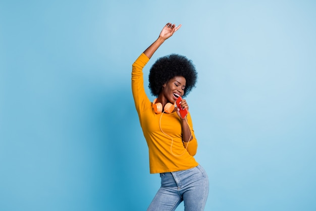 Fotoporträt einer schwarzhäutigen frau, die kopfhörer tanzt und dabei cellpnone nach oben zeigt, isoliert auf leuchtend blauem hintergrund
