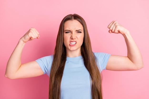 Fotoporträt einer wütenden frau, die sich beugt und bizeps zeigt, isoliert auf pastellrosafarbenem hintergrund