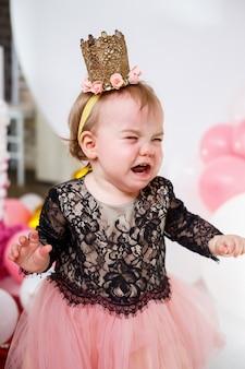 Fotoporträt eines 1-jährigen geburtstagsmädchens in einem rosa kleid mit rosa luftballons. das kind weint im urlaub, kindergefühle. mädchen weint