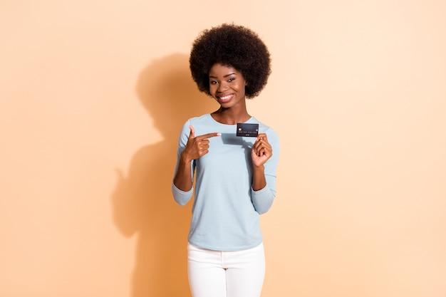 Fotoporträt eines dunkelhäutigen lächelnden mädchens, das mit dem finger auf eine plastik-debitkarte zeigt, die ein lässiges outfit trägt, isoliert auf beigefarbenem hintergrund