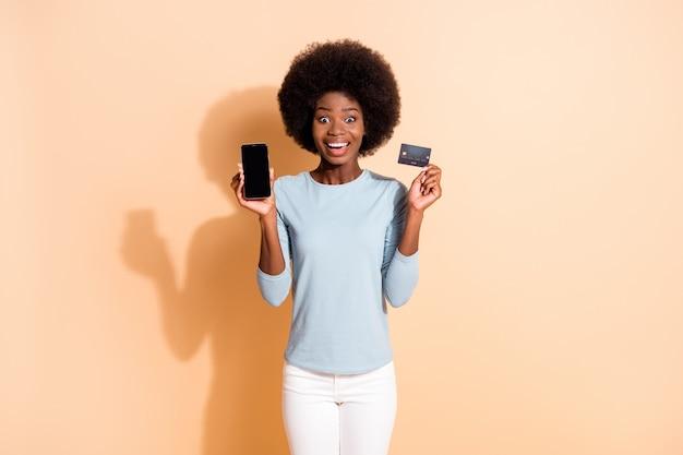 Fotoporträt eines dunkelhäutigen, lockigen mädchens, das erstaunt lächelt und die plastik-bankkarte des smartphone-bildschirms einzeln auf beigefarbenem hintergrund zeigt