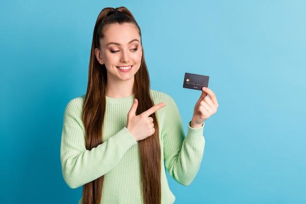 Fotoporträt eines mädchens, das mit dem finger auf die kreditkarte zeigt, die auf pastellblauem hintergrund isoliert ist?