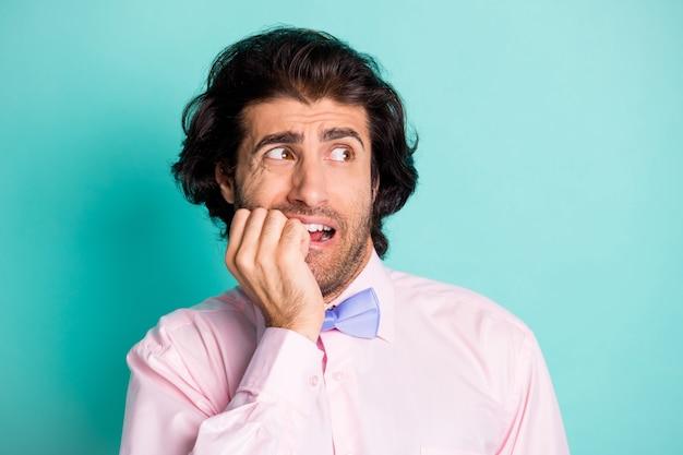 Fotoporträt eines mannes, der nägel beißt und zur seite schaut, isoliert auf pastellblauem hintergrund