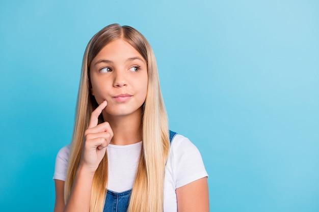 Fotoporträt eines nachdenklichen mädchens, das die gesichtswange mit dem finger berührt und auf den leeren raum schaut, der auf pastellblauem hintergrund isoliert ist?