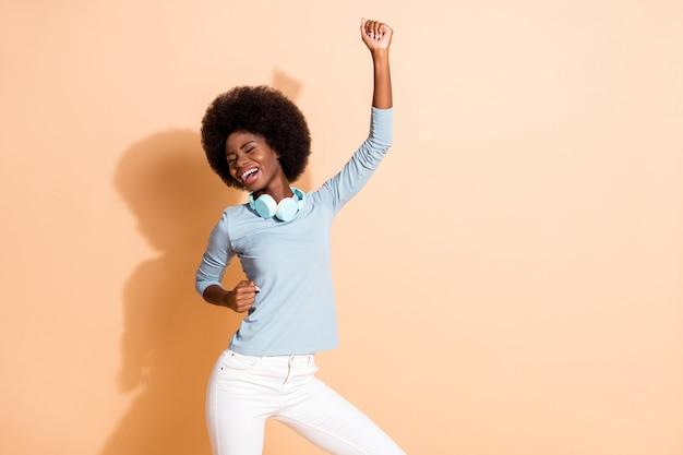 Fotoporträt eines unbeschwerten afroamerikanischen mädchens, das mit einer faust in der luft tanzt, isoliert auf pastellbeigem hintergrund