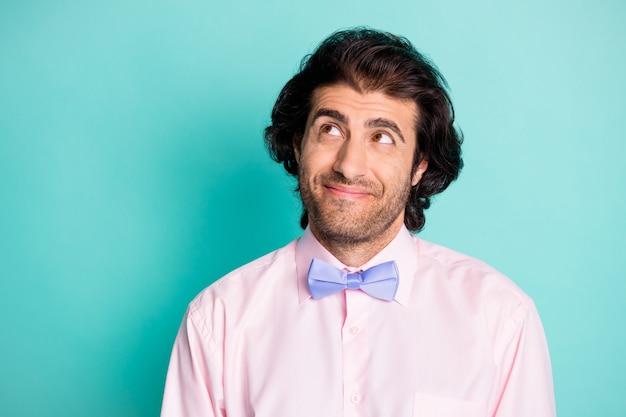 Fotoporträt eines verträumten kerls, der leerzeichen einzeln auf pastellblauem hintergrund anschaut