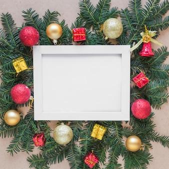 Fotorahmen auf tannenzweigen mit weihnachtsbällen