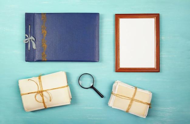 Fotorahmen, fotoalbum und alte fotos in einem stapel auf blauem holztisch, flach liegen