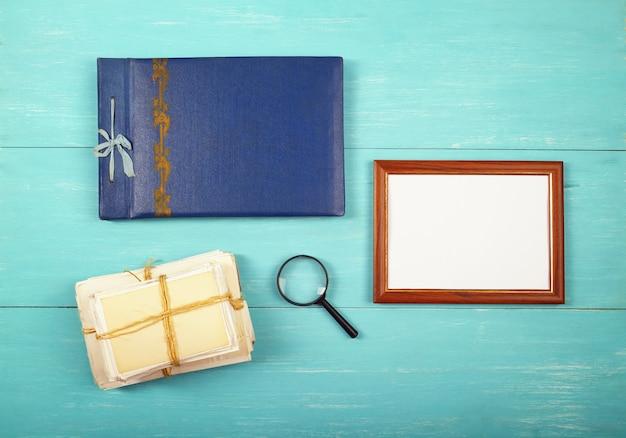 Fotorahmen-fotoalbum und alte fotos in einem stapel auf blauem holztisch