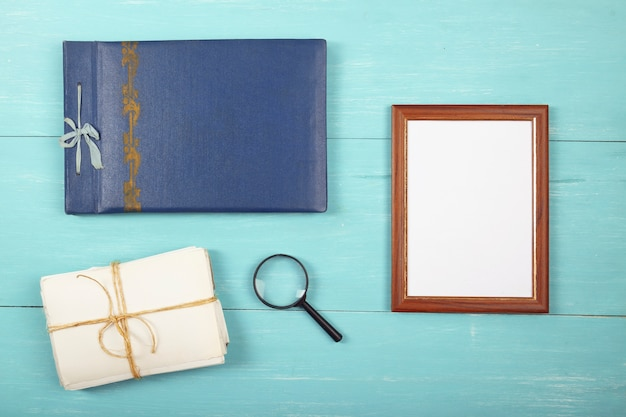 Fotorahmen fotoalbum und alte fotos in einem stapel auf blauem tisch, flach liegen