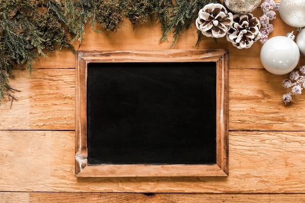 Fotorahmen in der nähe von nadelbäumen und weihnachtskugeln