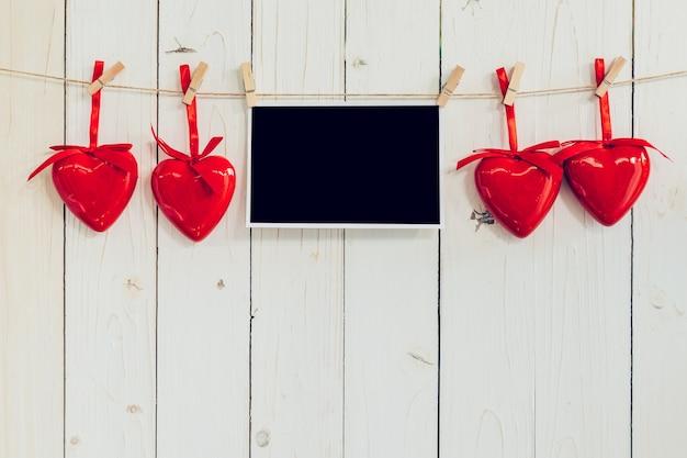 Fotorahmen leer und rotes herz hängen auf weißem holz hintergrund mit platz