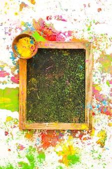 Fotorahmen mit farbe in der kleinen schüssel zwischen hellen trockenen farben