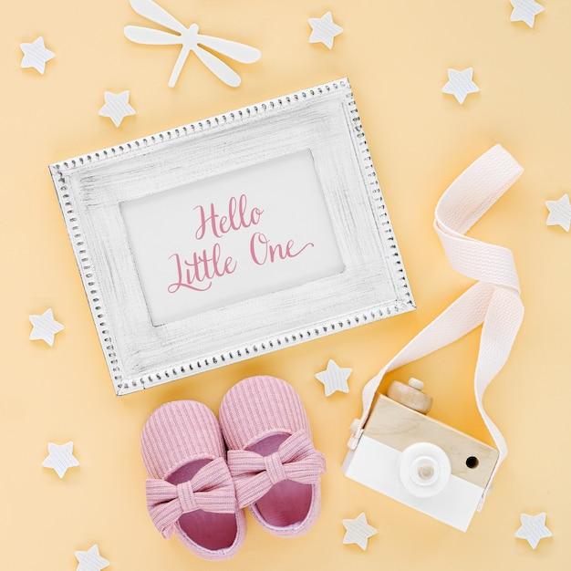 Fotorahmen mit karte hallo kleiner und babypantoffeln, spielzeug auf gelbem hintergrund. set neugeborenes zubehör für mädchen. flache lage, ansicht von oben