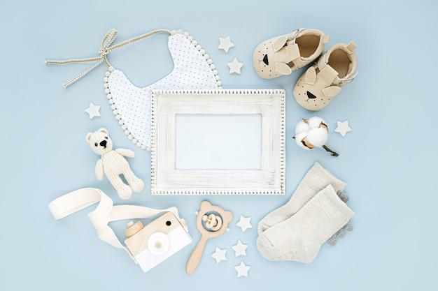 Fotorahmen mit kleidung und accessoires für neugeborene jungen. spielzeug, socken und babyschuhe mit lätzchen auf blauem hintergrund. baby-dusche-konzept. mock-up-tor-text. flache lage, ansicht von oben