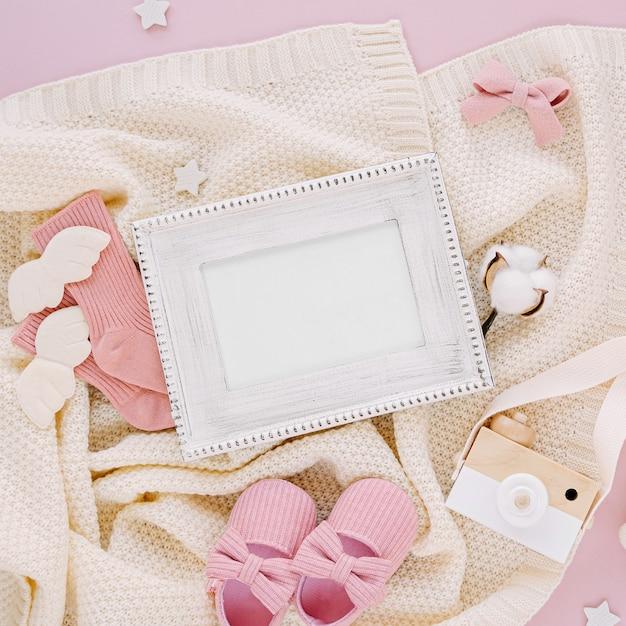 Fotorahmen mit kleidung und accessoires für neugeborene. spielzeug, socken und babyschuhe mit gestrickter decke auf rosa hintergrund. baby-dusche-konzept. mock-up-tor-text. flache lage, ansicht von oben