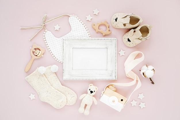 Fotorahmen mit kleidung und accessoires für neugeborenes mädchen. spielzeug, socken und babyschuhe mit lätzchen auf rosa hintergrund. mock-up-tor-text. baby-dusche-konzept. flache lage, ansicht von oben