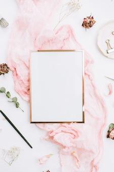 Fotorahmen mit kopienraum auf rosa decke mit eukalyptuszweigen und rosenblüten auf weißem hintergrund. flache lage, ansicht von oben