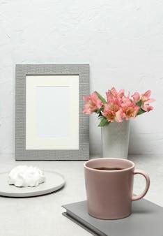 Fotorahmen mit rosa blumen, schalenkaffee, kuchen auf grauer tabelle