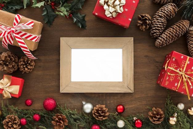 Fotorahmen nahe tannenzweigen, baumstümpfen, geschenken und weihnachtsspielwaren