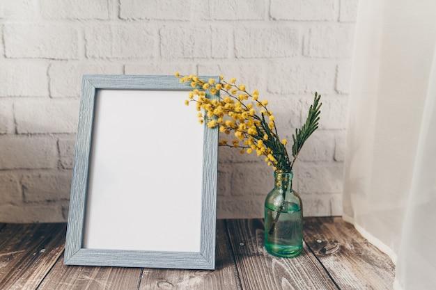 Fotorahmen und eine kleine flasche mit mimose auf einer mauer