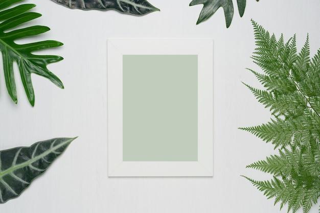 Fotorahmen und grünblätter auf einem weißen hölzernen hintergrund