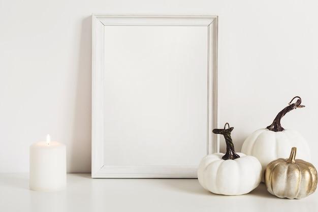 Fotorahmen und weiße kürbisse. mockup kopieren sie platz für kunstwerke. herbstdekor im innenraum.