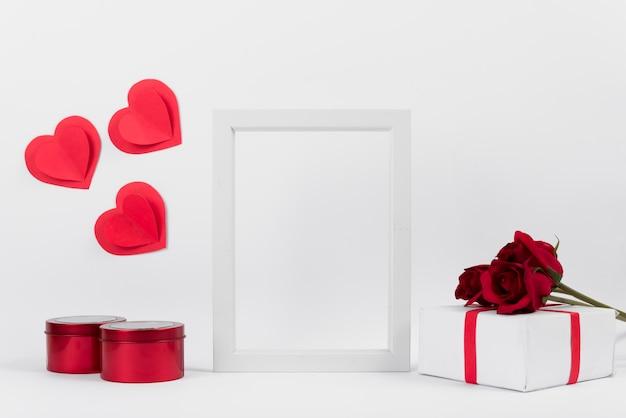 Fotorahmen zwischen geschenk mit blumen, papierherzen und kästen