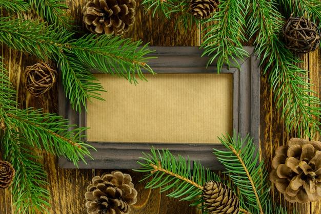 Fotorahmen zwischen weihnachtsdekoration, mit kiefernkegeln auf einem braunen holztisch. draufsicht, feld, zum des raumes zu kopieren.
