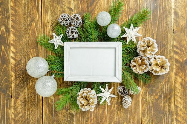Fotorahmen zwischen weihnachtsdekoration, mit weißen bällen und kiefernkegeln auf einem braunen holztisch. draufsicht, feld, zum des raumes zu kopieren.