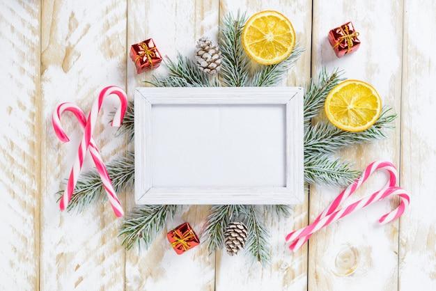 Fotorahmen zwischen weihnachtsdekoration, mit zuckerstangen und geschenkboxen auf einem weißen holztisch. draufsicht, feld, zum des raumes zu kopieren