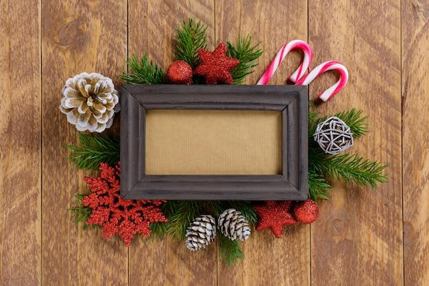 Fotorahmen zwischen weihnachtsdekoration, mit zuckerstangen und kiefernkegeln auf einem braunen holztisch. draufsicht, feld, zum des raumes zu kopieren