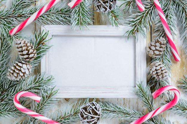Fotorahmen zwischen weihnachtsdekoration, mit zuckerstangen und kiefernkegeln auf einem weißen holztisch. draufsicht, feld, zum des raumes zu kopieren