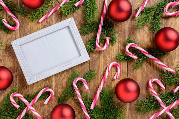 Fotorahmen zwischen weihnachtsdekoration, mit zuckerstangen und roten bällen auf einem braunen holztisch. draufsicht, feld, zum des raumes zu kopieren