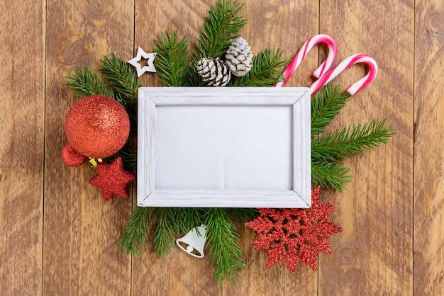 Fotorahmen zwischen weihnachtsdekoration, mit zuckerstangen und zahlen auf einem braunen holztisch. draufsicht, feld, zum des raumes zu kopieren