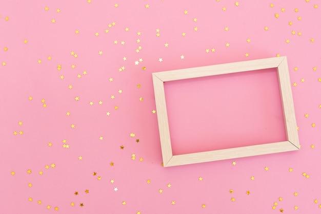 Fotorahmenspott oben mit raum für text, goldene paillettekonfettis auf rosa hintergrund.