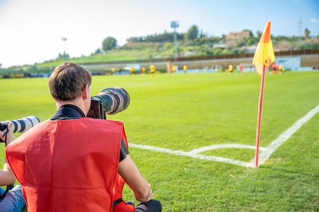 Fotoreporter mit teleobjektiv auf einem fußballspiel